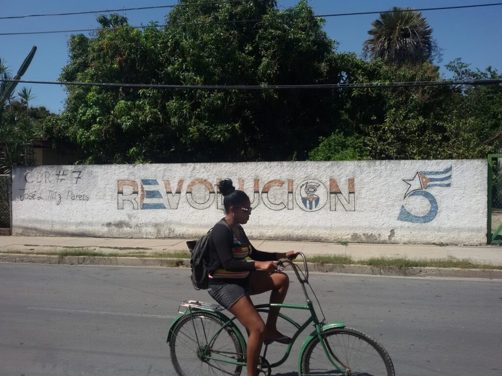 Woman riding a bike in Cienfuegos in Cuba. Illustration of a Complete Guide from Coast to Coast.