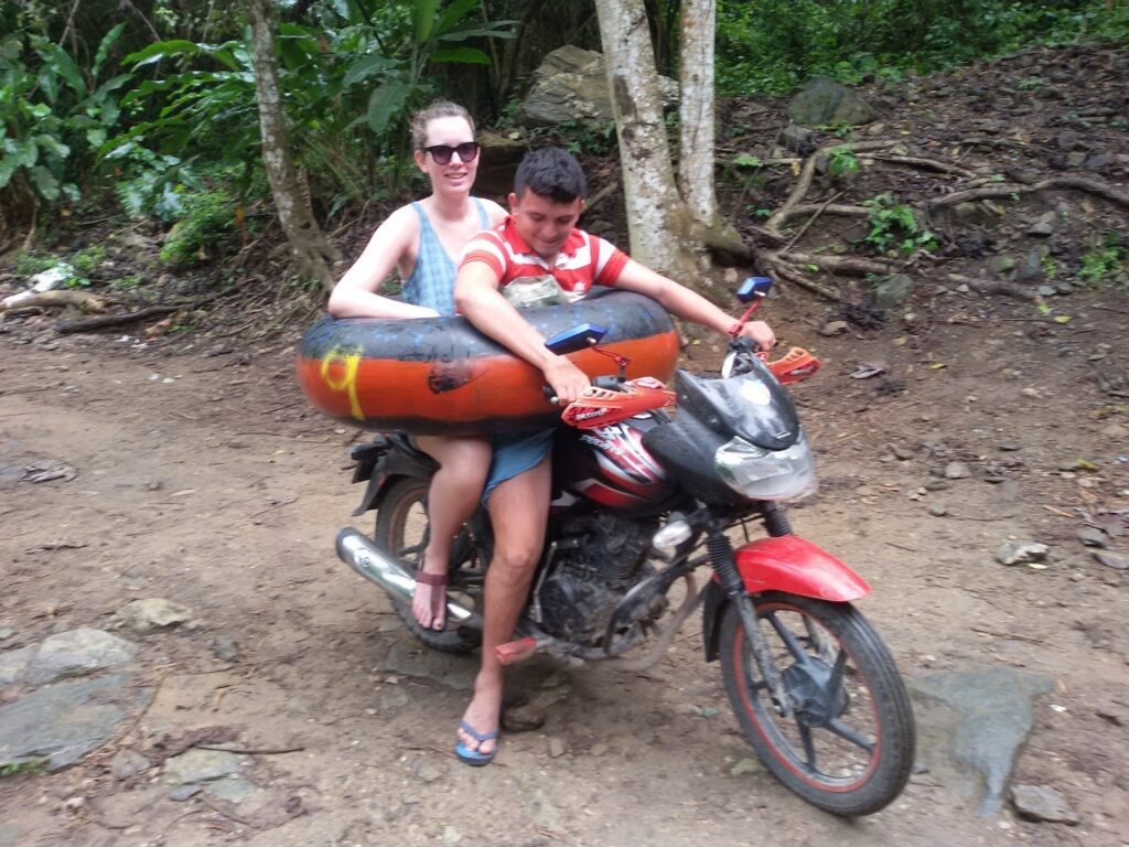 Two people sitting on a motobike with a tire around their waste.
