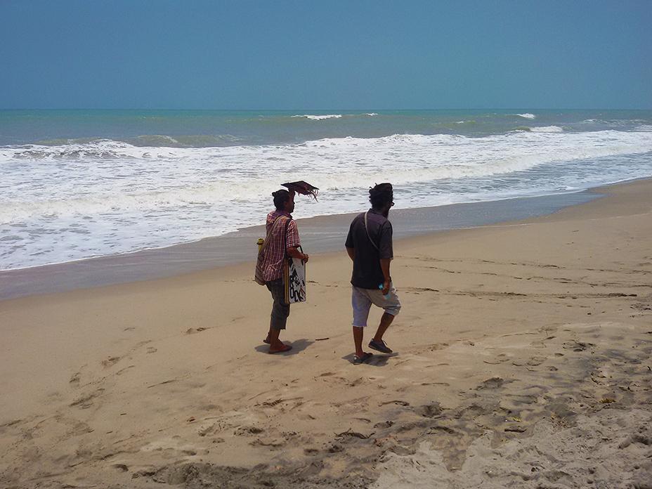 Two men walking on the beach of Palomino
