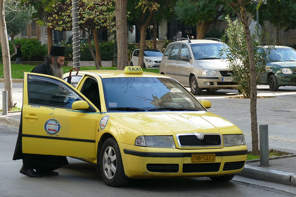 Greek cleric getting into a cab
