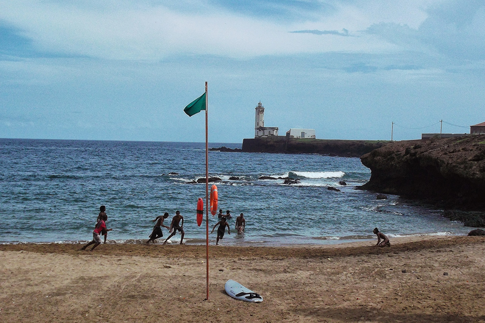 Locals playing soccer on one of the Praia's city beaches in the backdrop of the lighthouse.