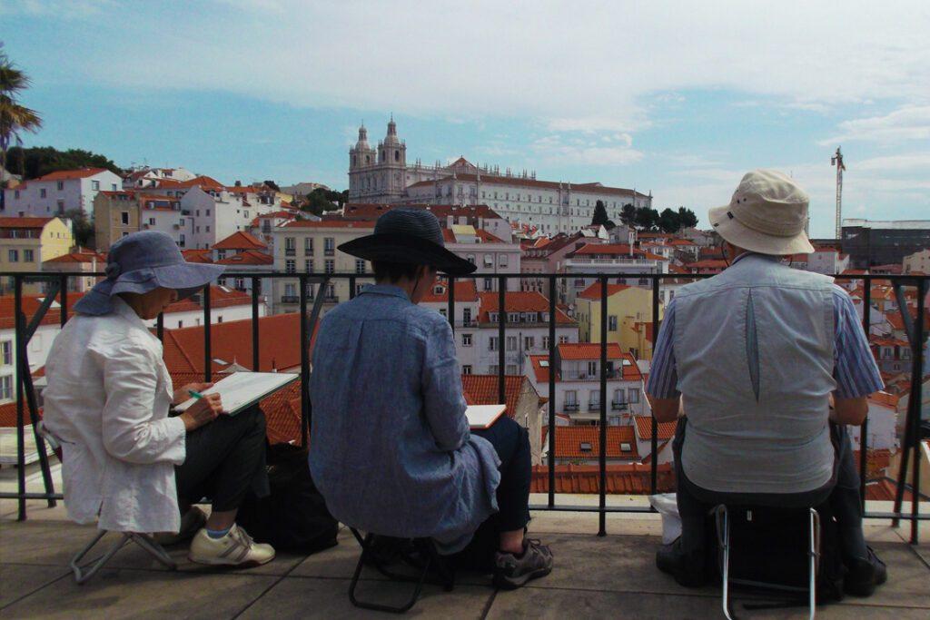 Asian tourist painting Lisbon's  Church and Monastery of São Vicente de Fora.