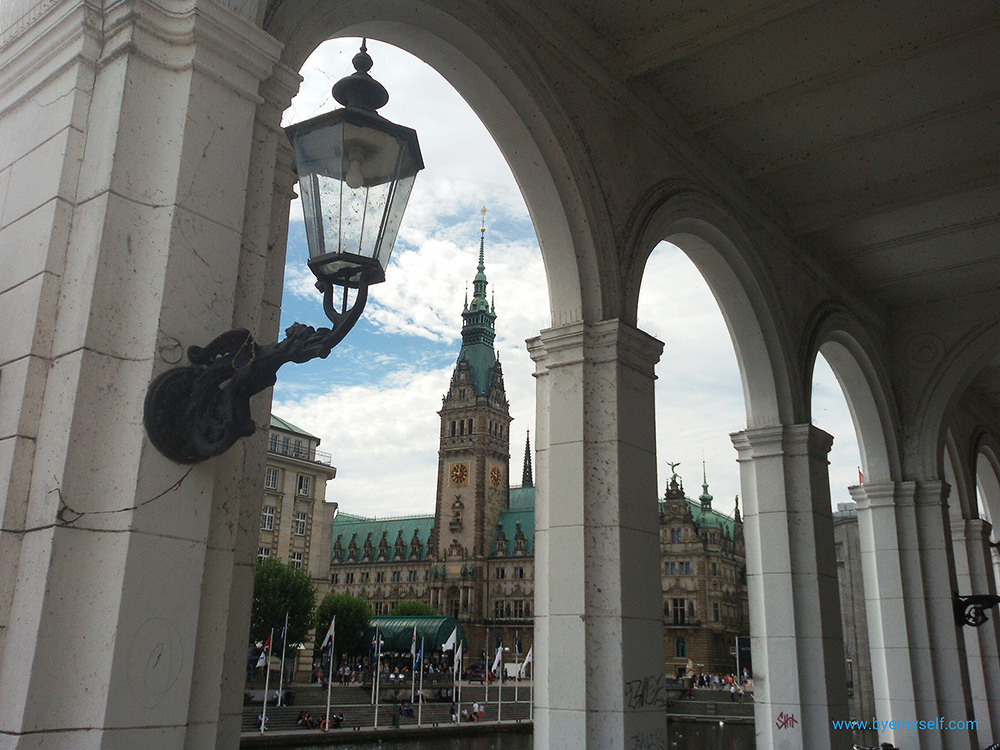 Hamburg town hall, seen from the adjacent Alsterarkaden, the Alster arcades, housing posh cafés, and specialty shops.