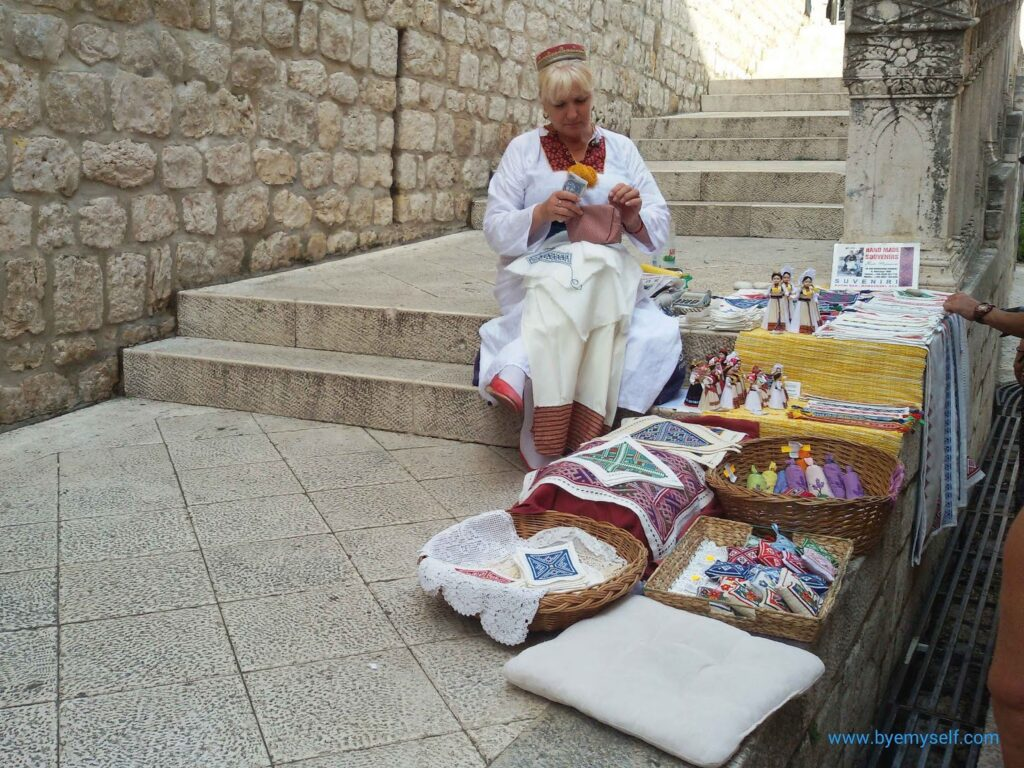 A lady wearing traditional attire selling regional handicraft in Dubrovnik Croatia Dalmatia