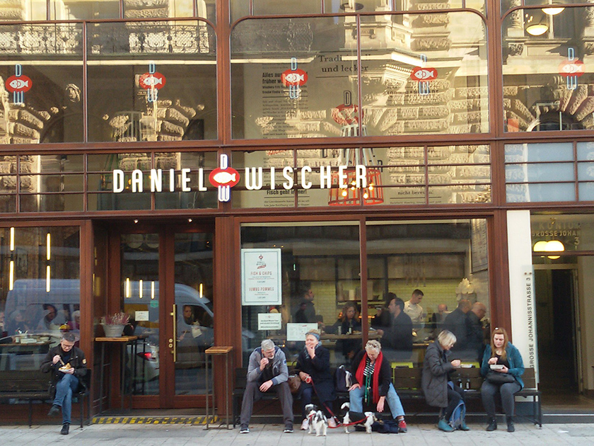People eating fish in front of Daniel Wischer restaurant in Hamburg - illustrating a Comprehensive Guide to Hamburg